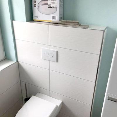 Toilette mit großen weißen Fliesen